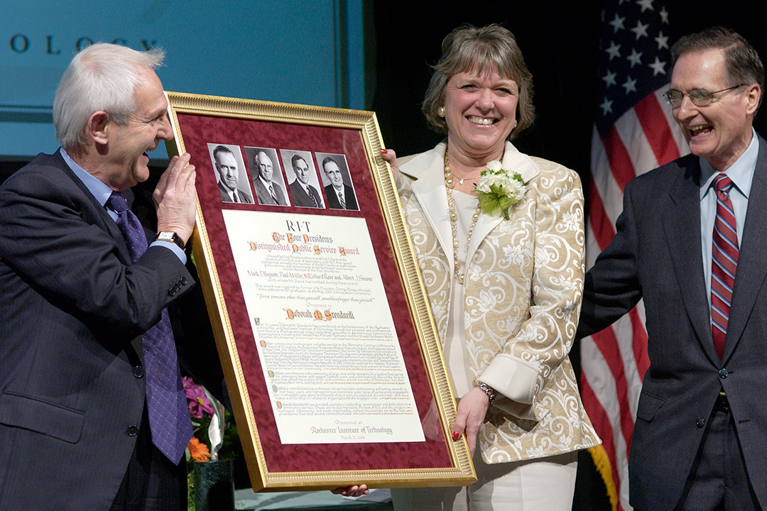 woman and man holding large framed award