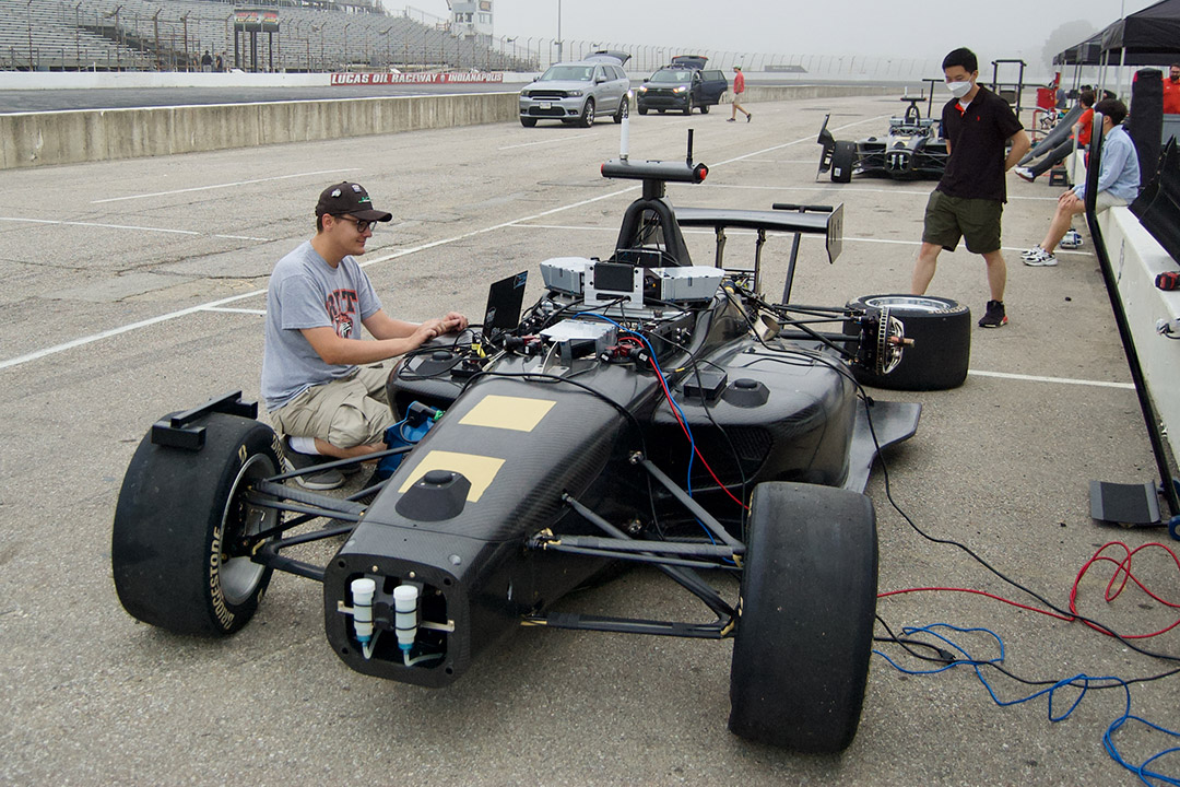 student working on wheel of Indy racecar.