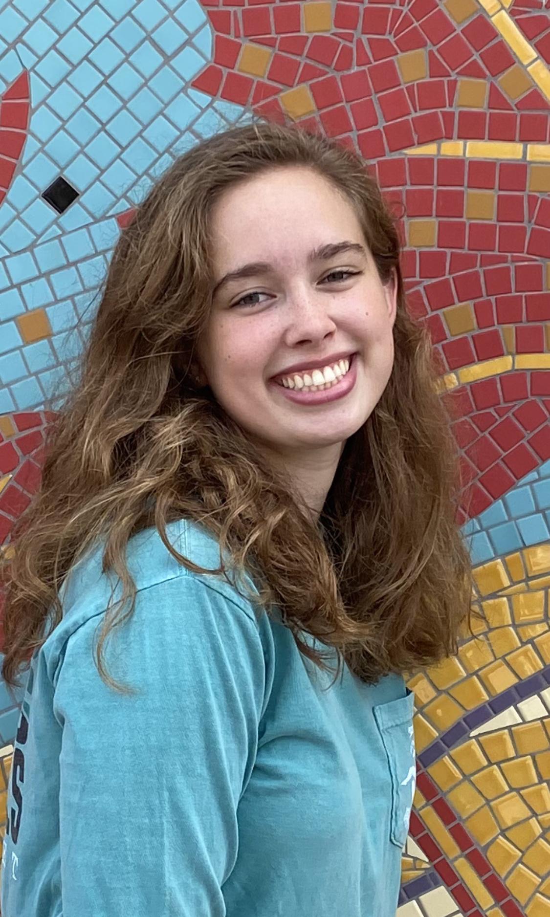 Devon Scott-Davis photographed against a colorful wall.