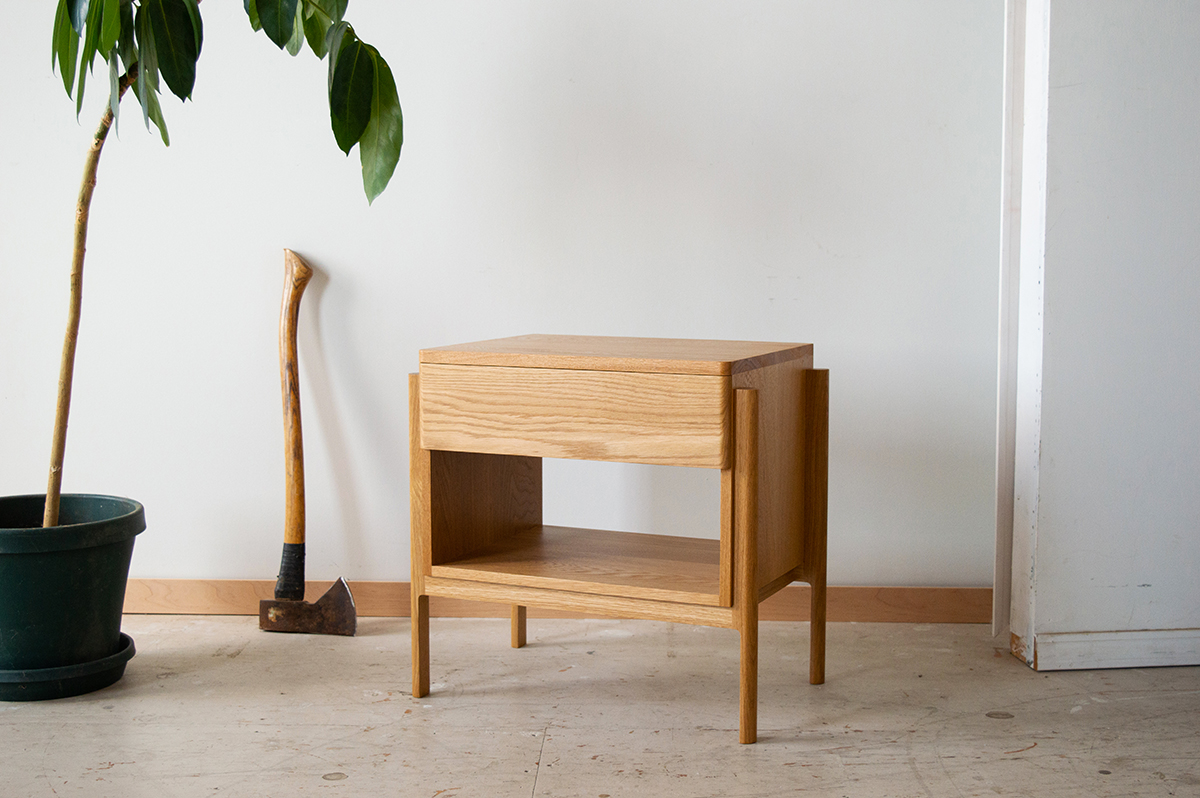 A well-crafted nightstand sits in a space next to a plant.