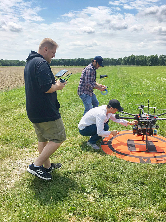 Researchers set up drone in farmers field.