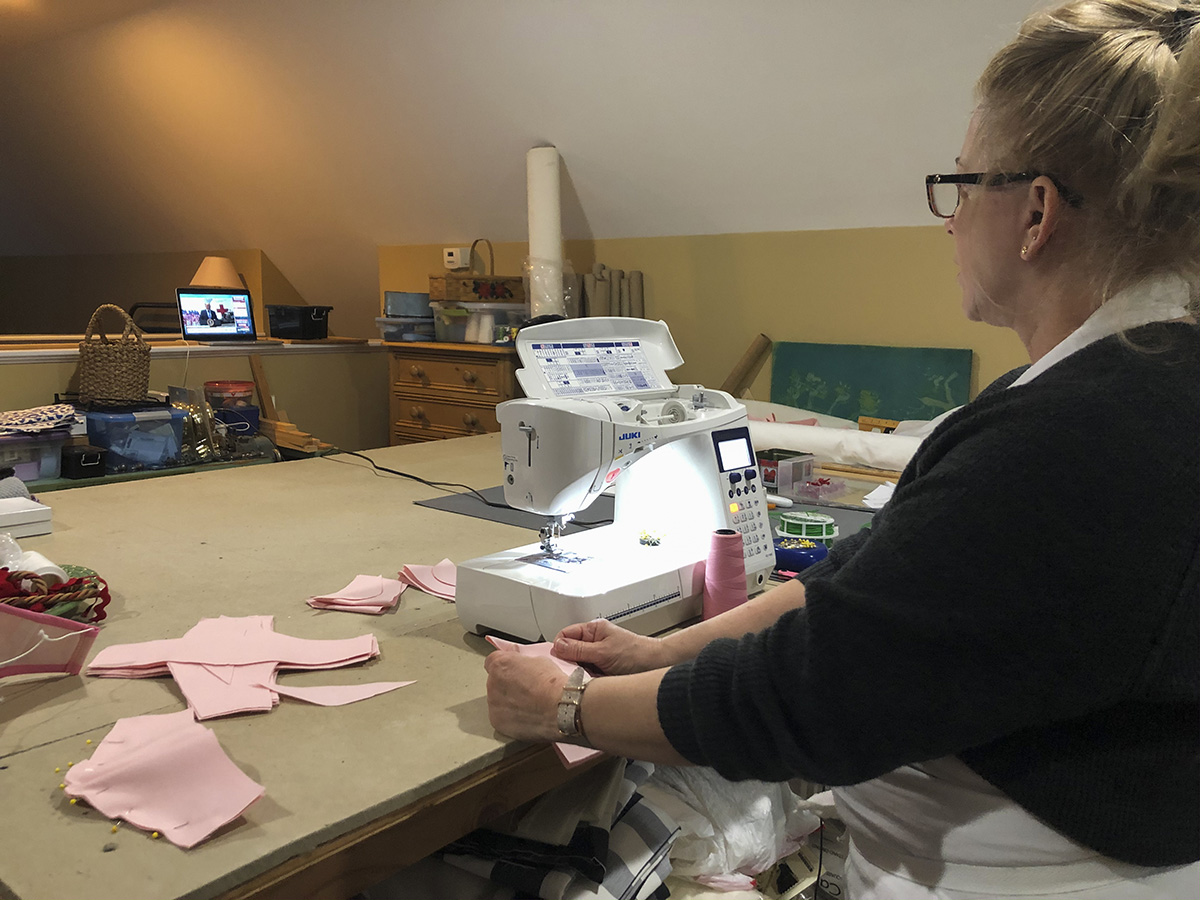 A woman sews fabrics together.