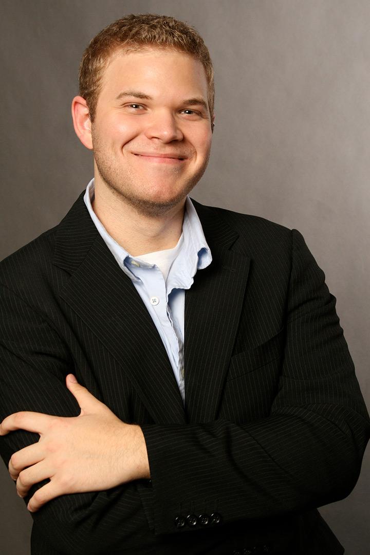 Smiling man wearing black suit jacket and blue shirt