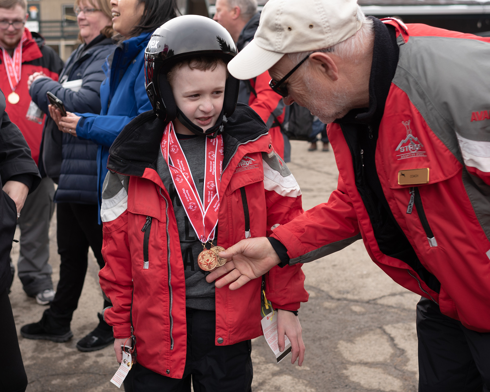 Coach, Marcel Chaine, congratulates Matthew Duffy on his metals for alpine skiing.