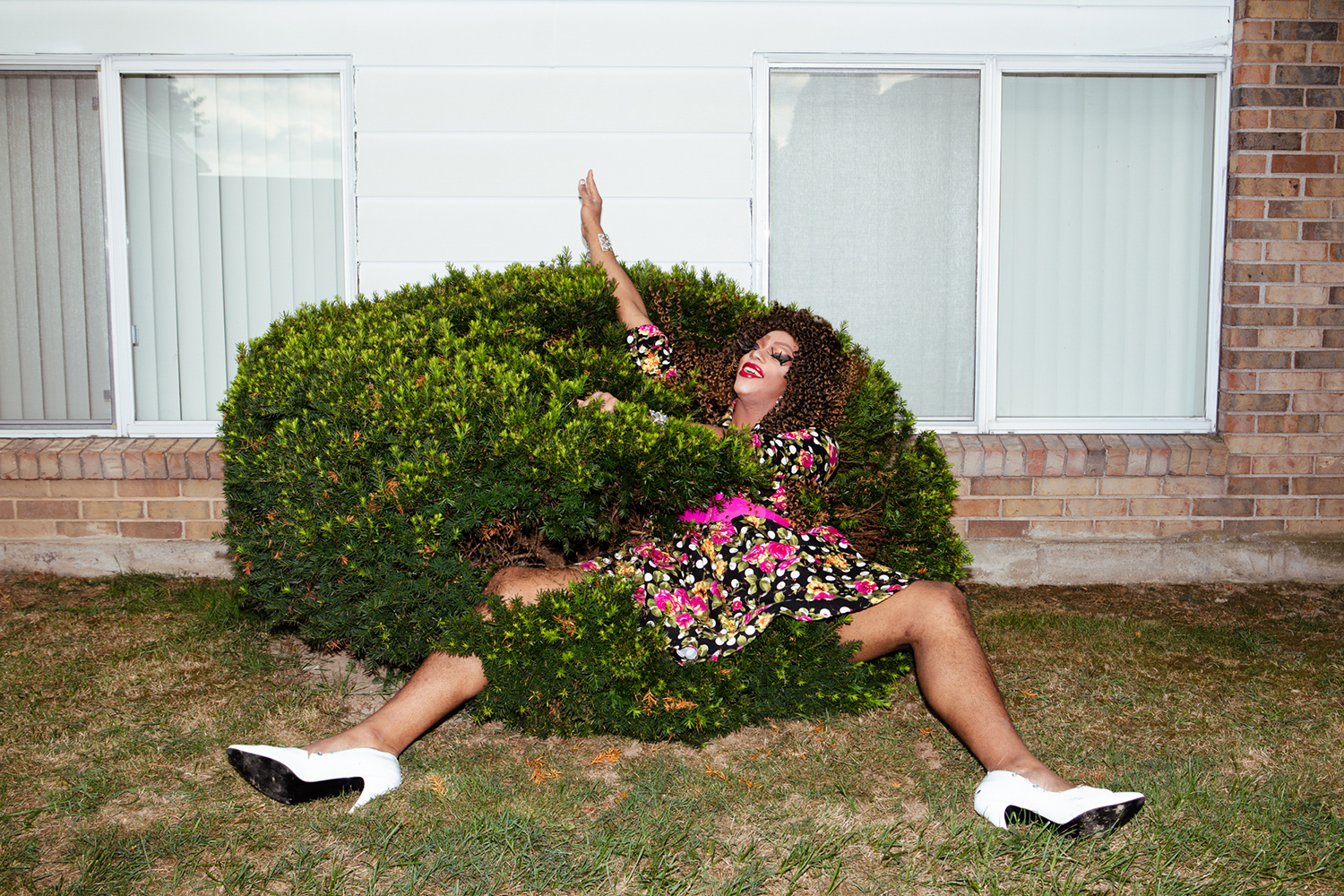 A dress-clad woman sitting in a bush.