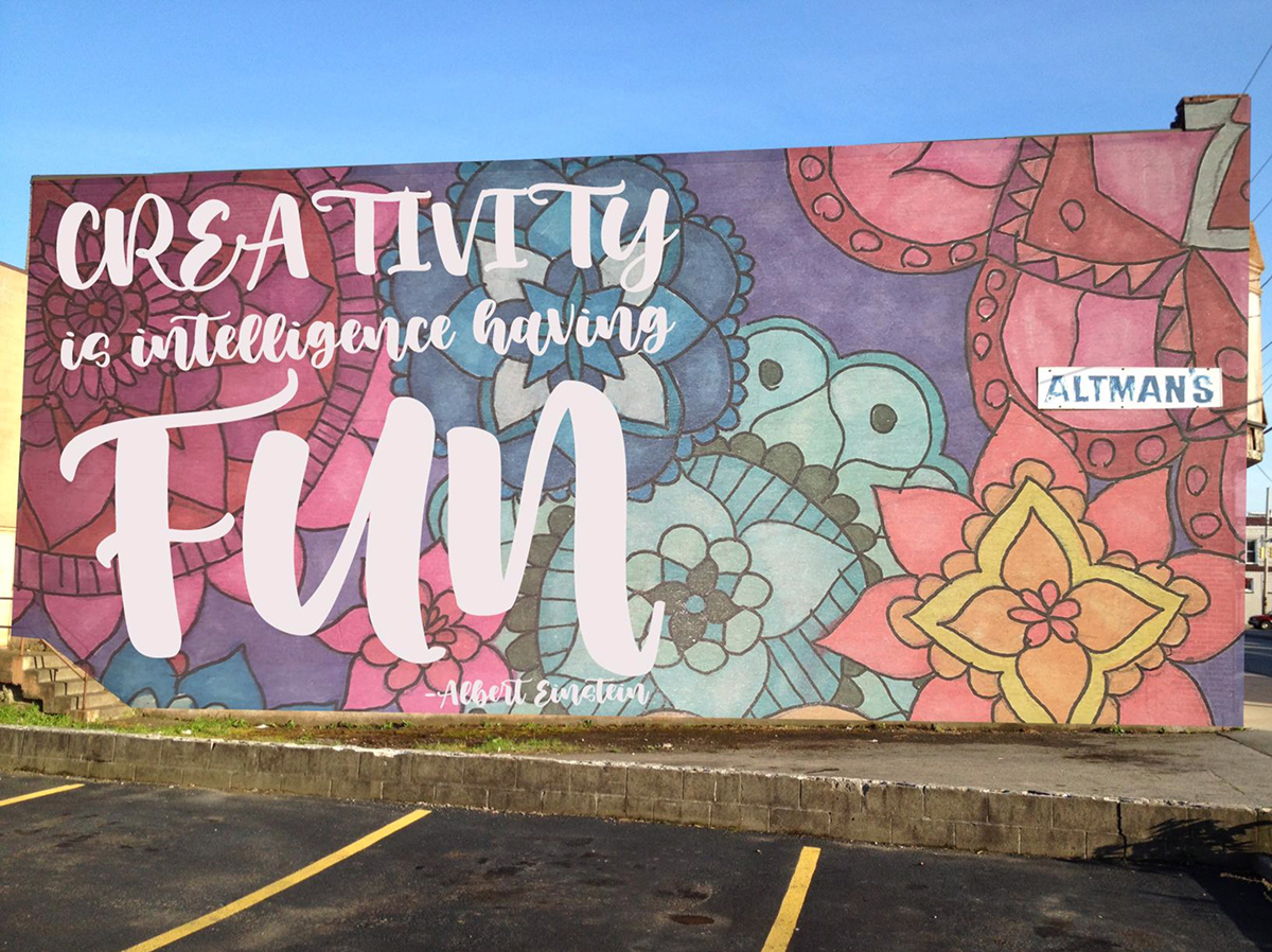 "A colorful mural with the words ""Creativity is Intelligence Having Fun."""