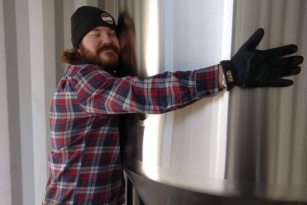 man hugging vat of beer.