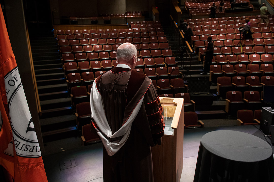 President Munson delivering speech in front of empty auditorium.