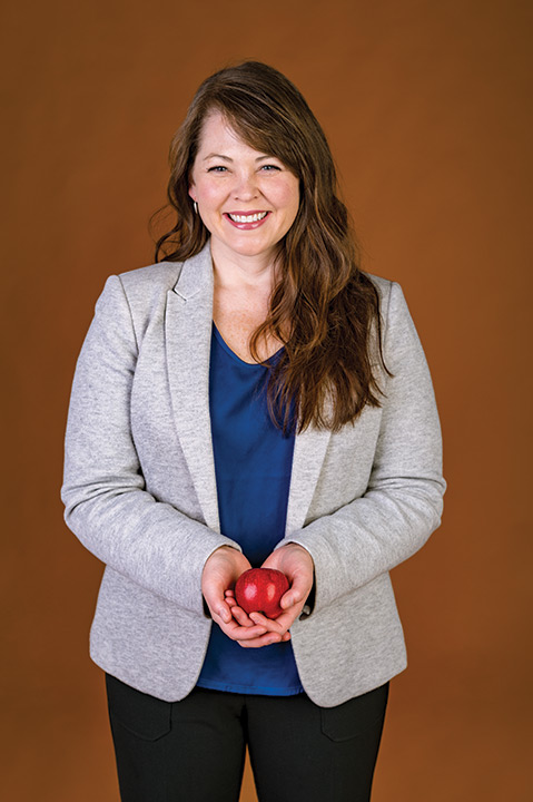 Woman holds apple.