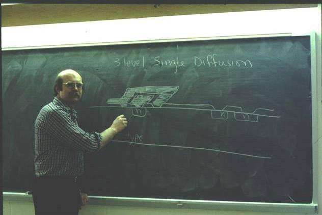 professor writing on chalkboard in the 1970s.