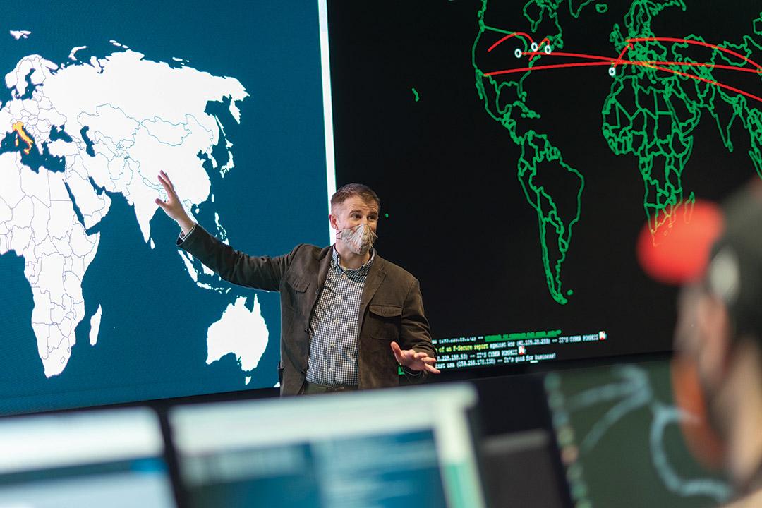 professor gesturing toward a world map.