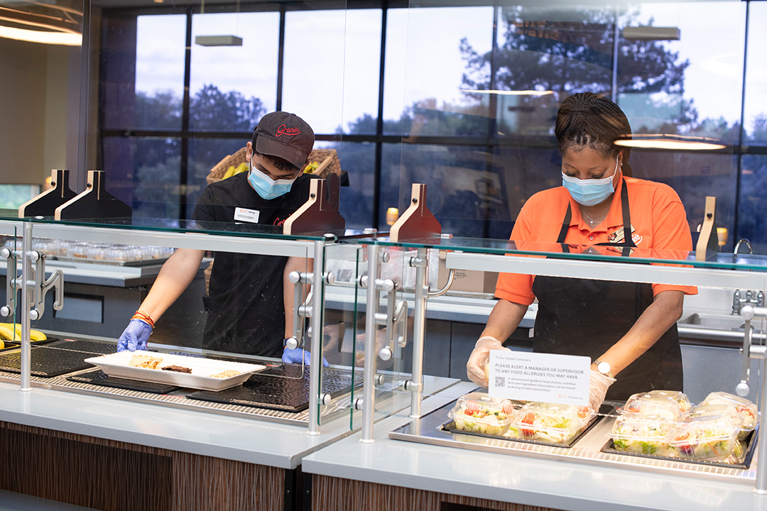 two food workers prepare a meal in a cafeteria.