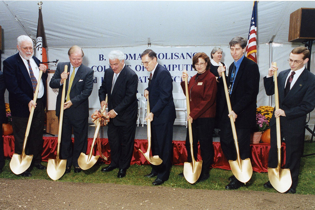 seven people lined up holding golden shovels for a ceremonial groundbreaking.