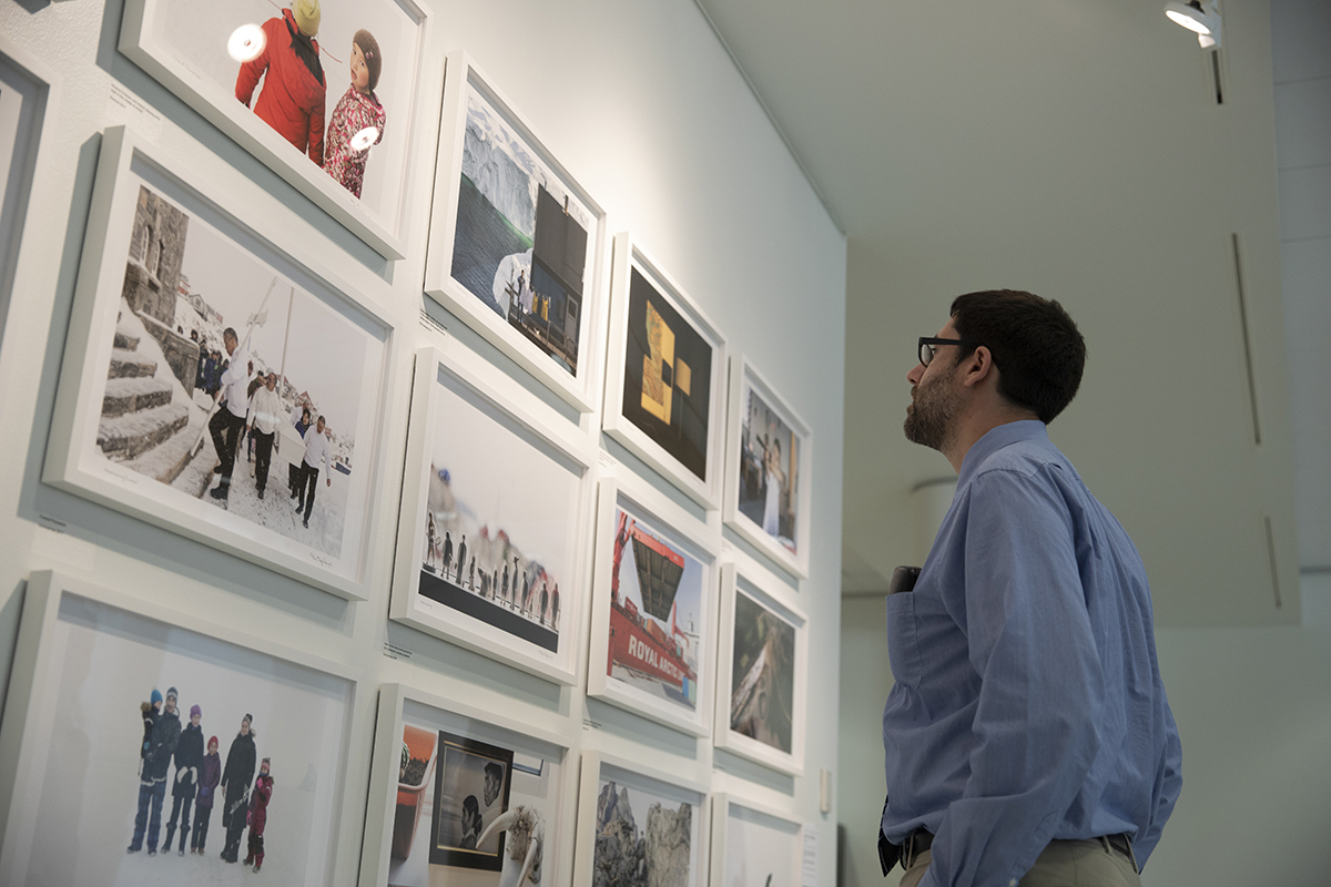 A person looks at a wall full of Denis Defibaugh's Greenland photos as they are displayed in University Gallery. The photo was taken as part of Denis Defibaugh's NSF grant.