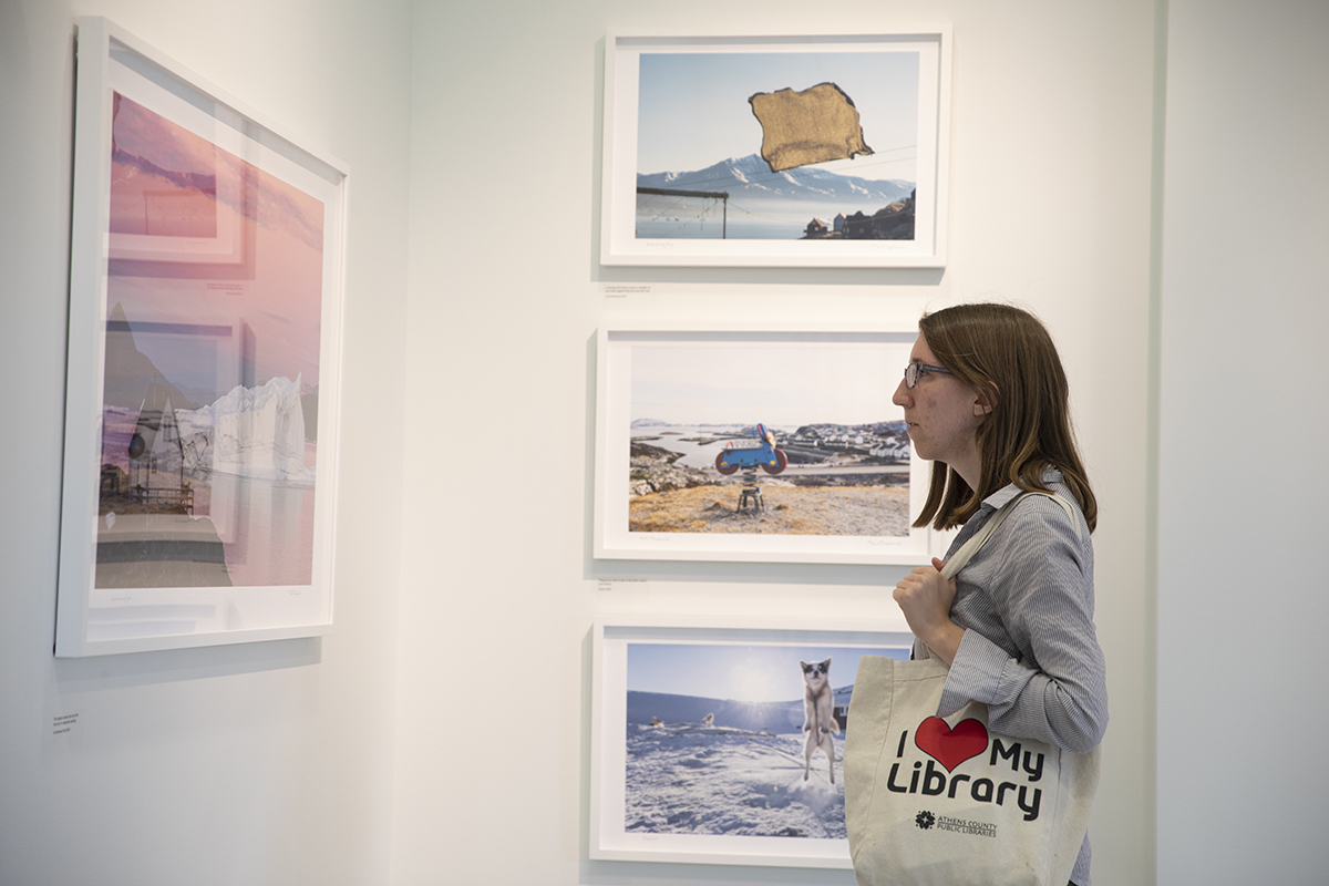 A University Gallery visitor closely observes a Greenland photo by Denis Defibaugh. The photo was taken as part of Denis Defibaugh's NSF grant.