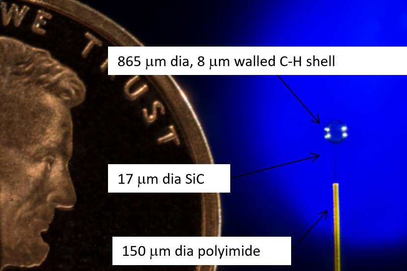 860 micro-meter diameter plastic shell supported by a 17-micro meter silicon carbide fiber.