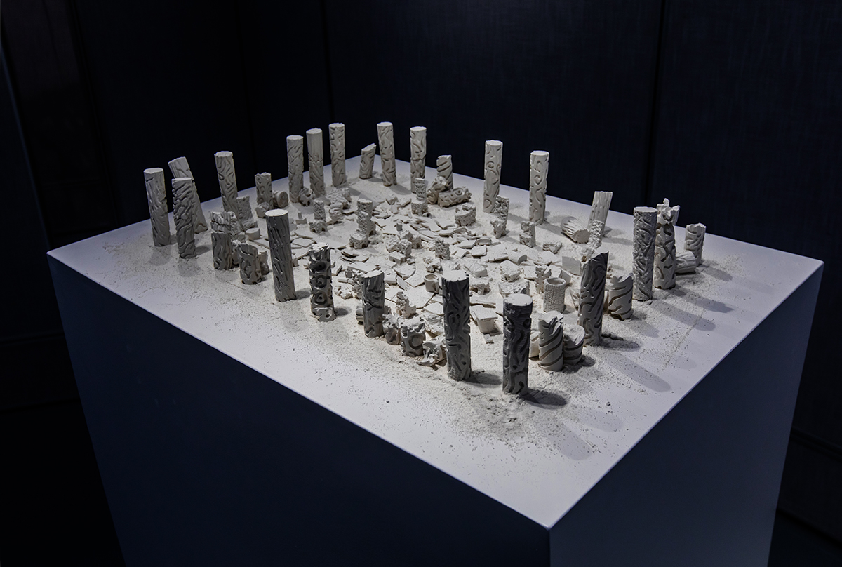 A group of small, cylinder-shaped sculptures stand on a tall surface.