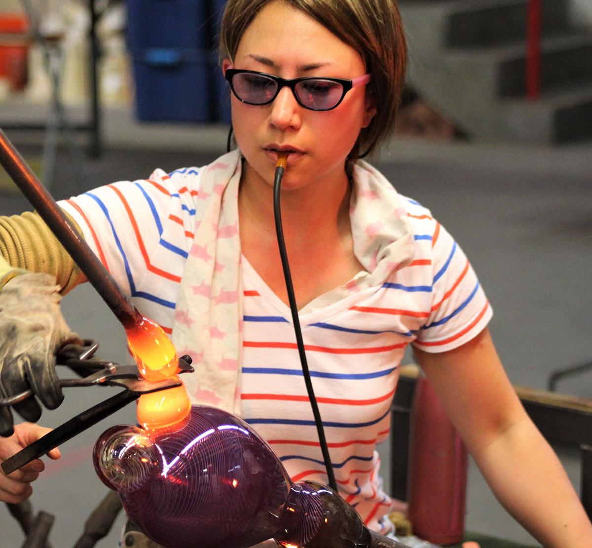 Aya Oki blows glass in a studio.