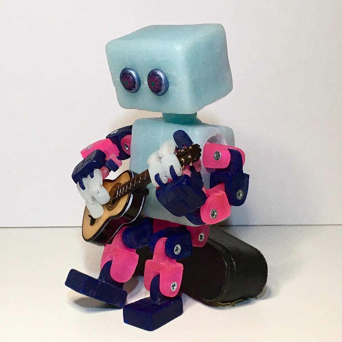 A toy robot sculpture plays a guitar.