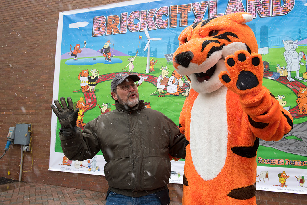 Man poses with Tiger mascot in front of mural.