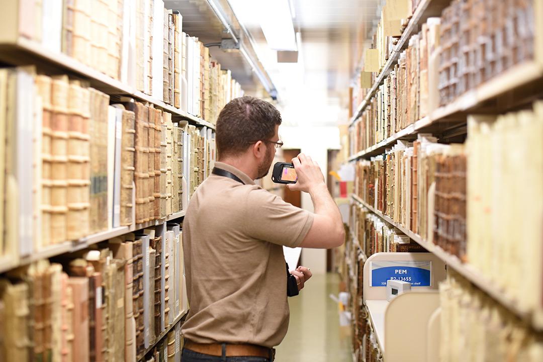 Man takes cellphone photo amid tall racks of files.