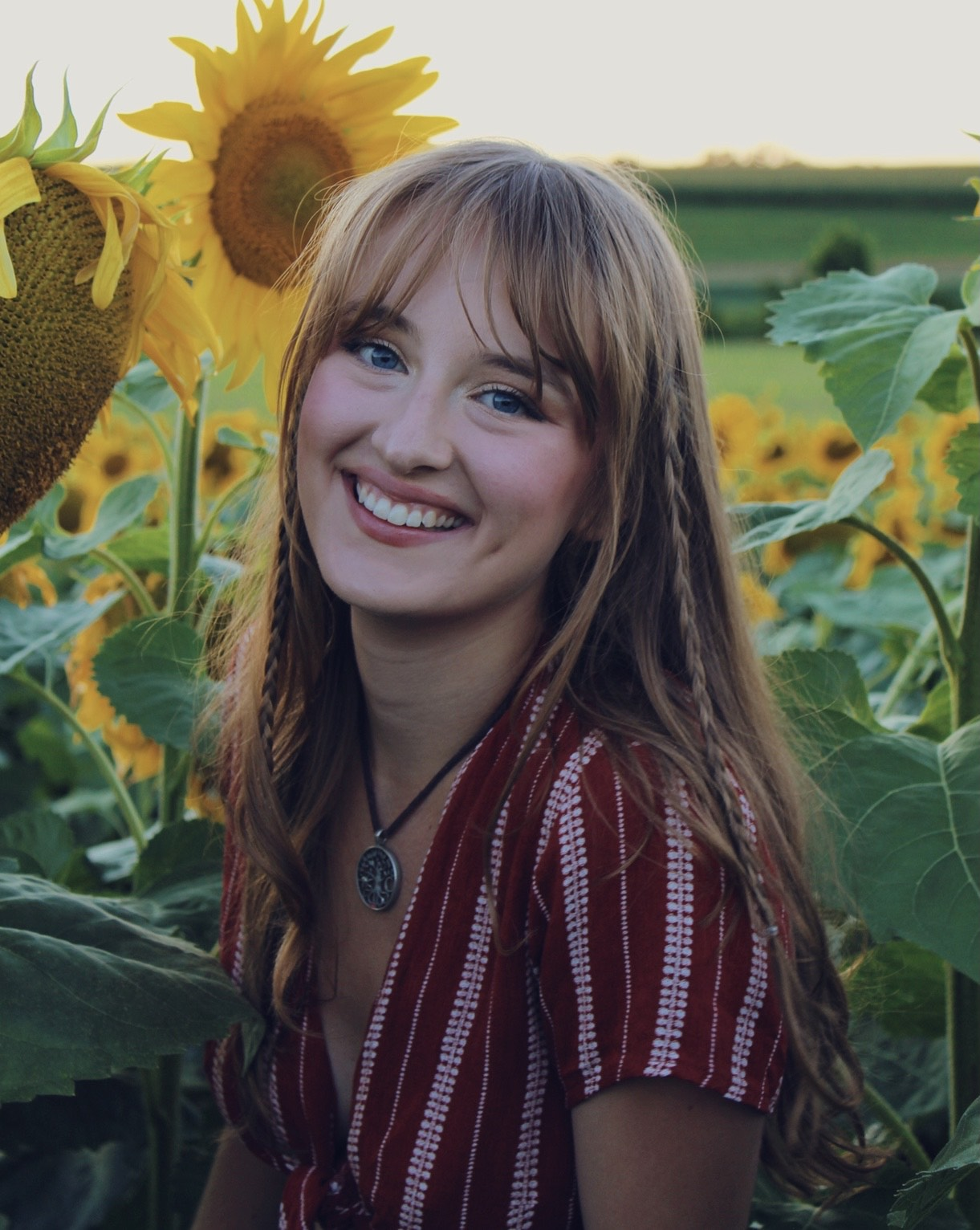 A headshot of Isabelle Anderson in a field of sunflowers.