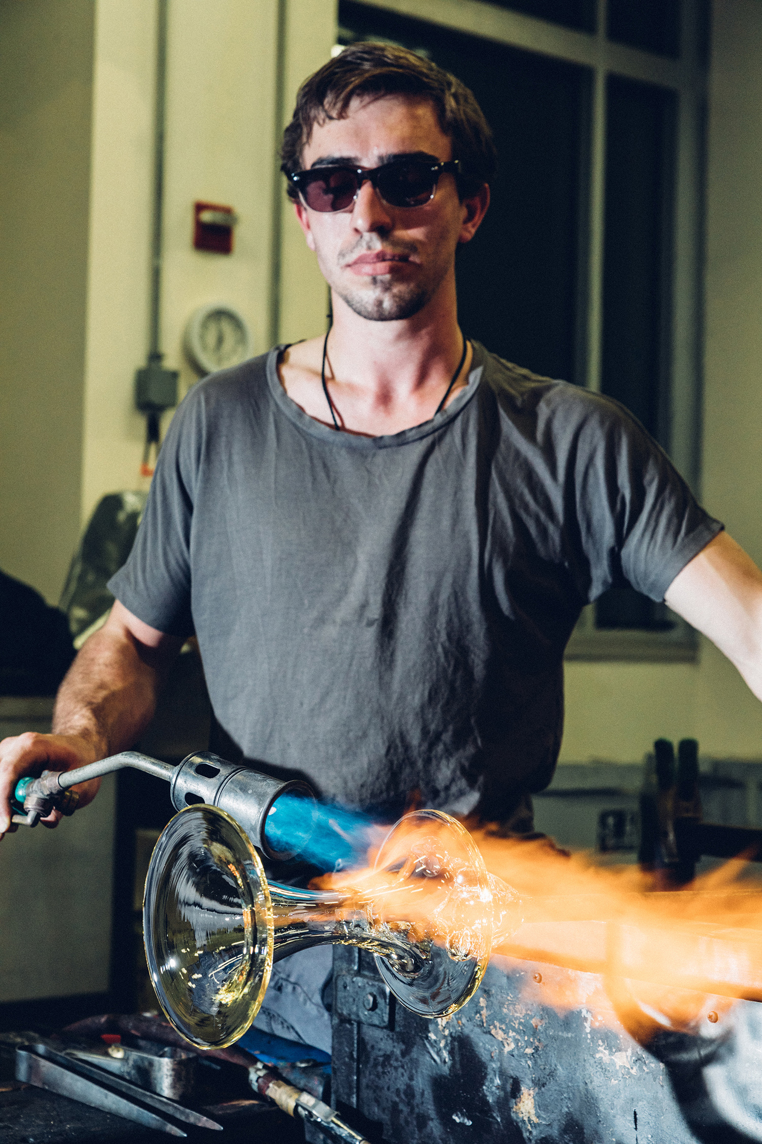 A student puts a torch to a project in the glass hot shop.