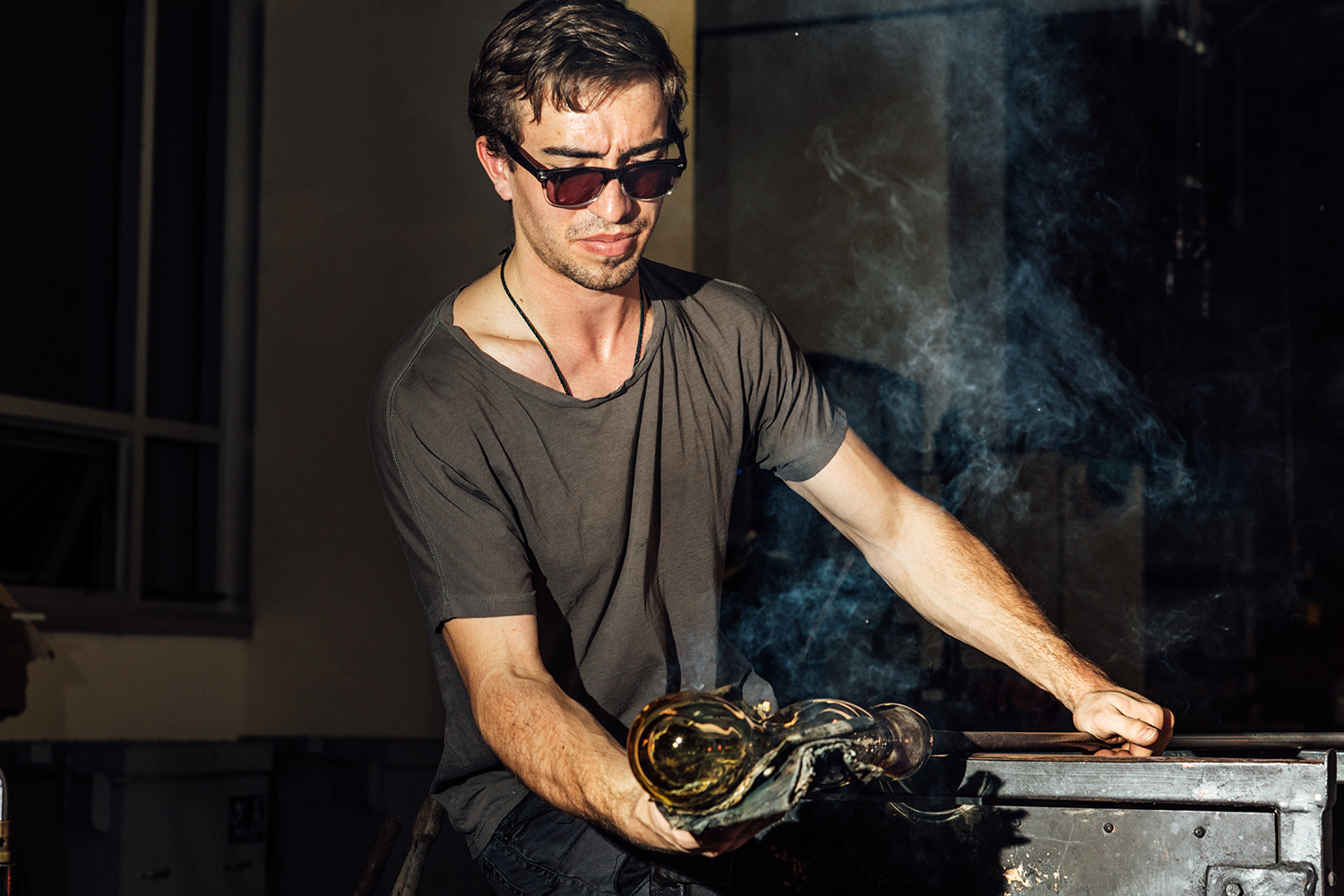 A student works in the glass hot shop