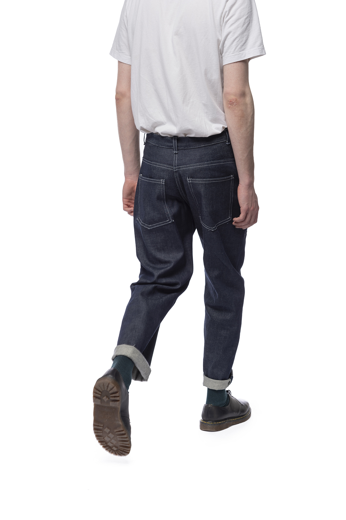 Functional clothing design of jeans that are rolled just above a model's ankles.