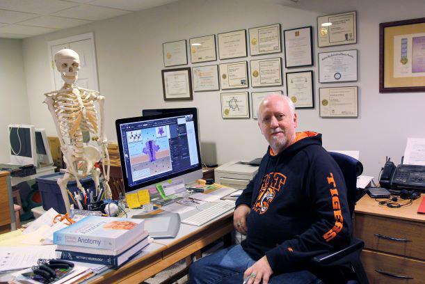 professor sitting at desk facing a model of a human skeleton.