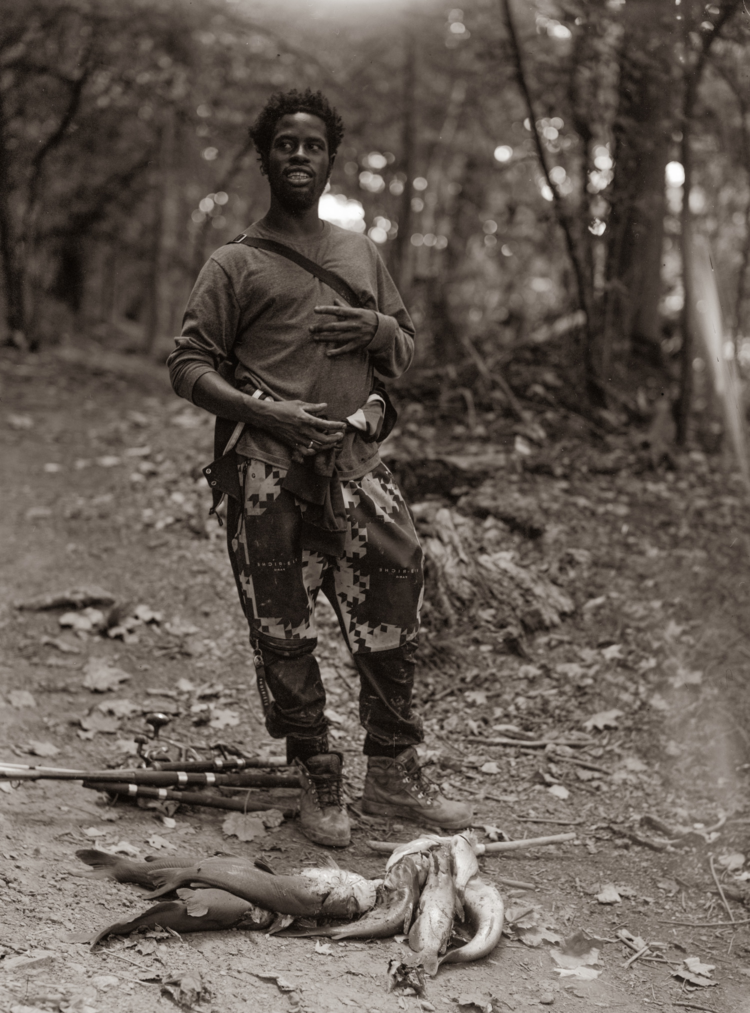 A fisherman stands in the woods next to fish he caught.
