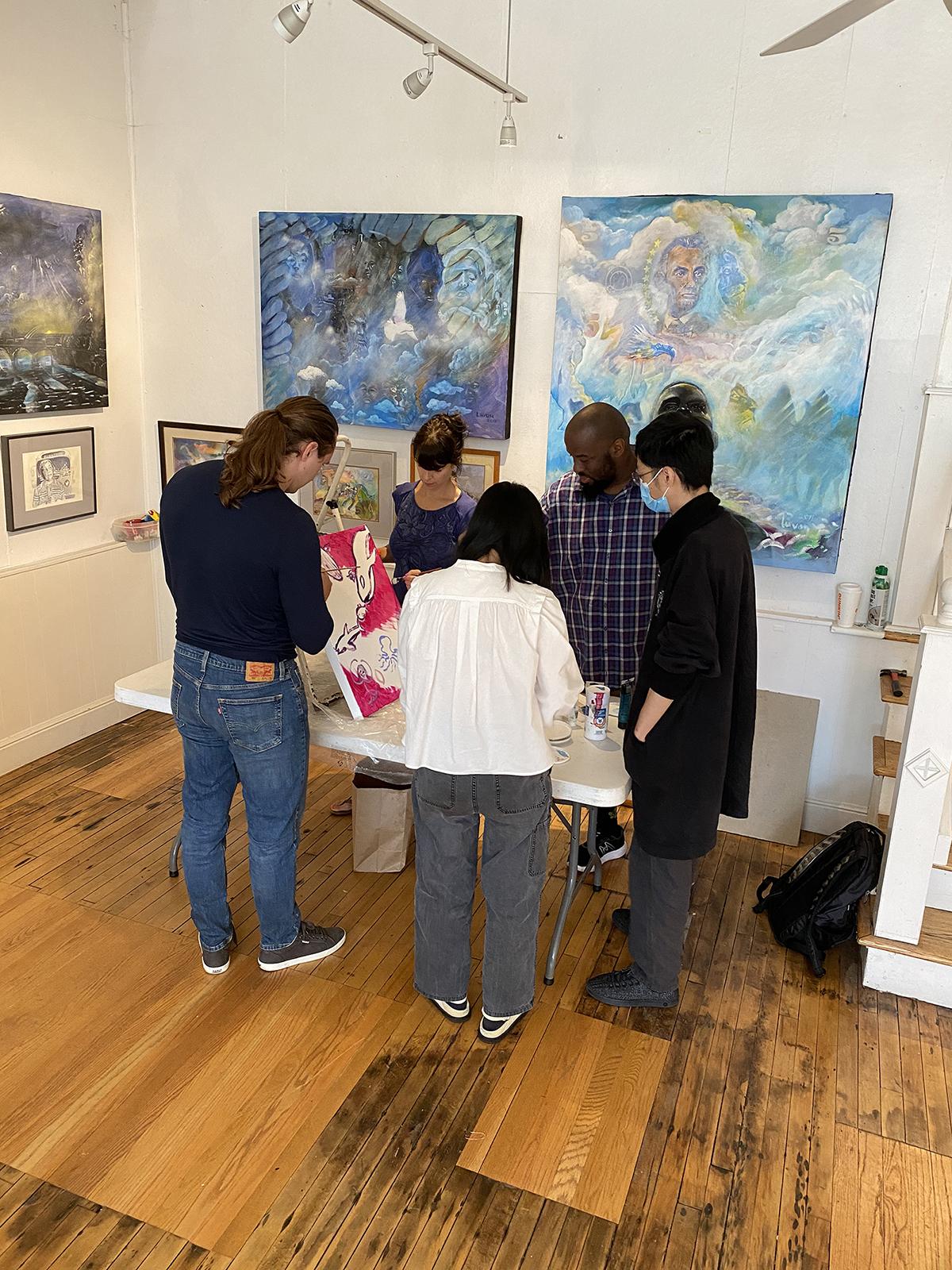 A group of artists talk inside Joy Gallery.