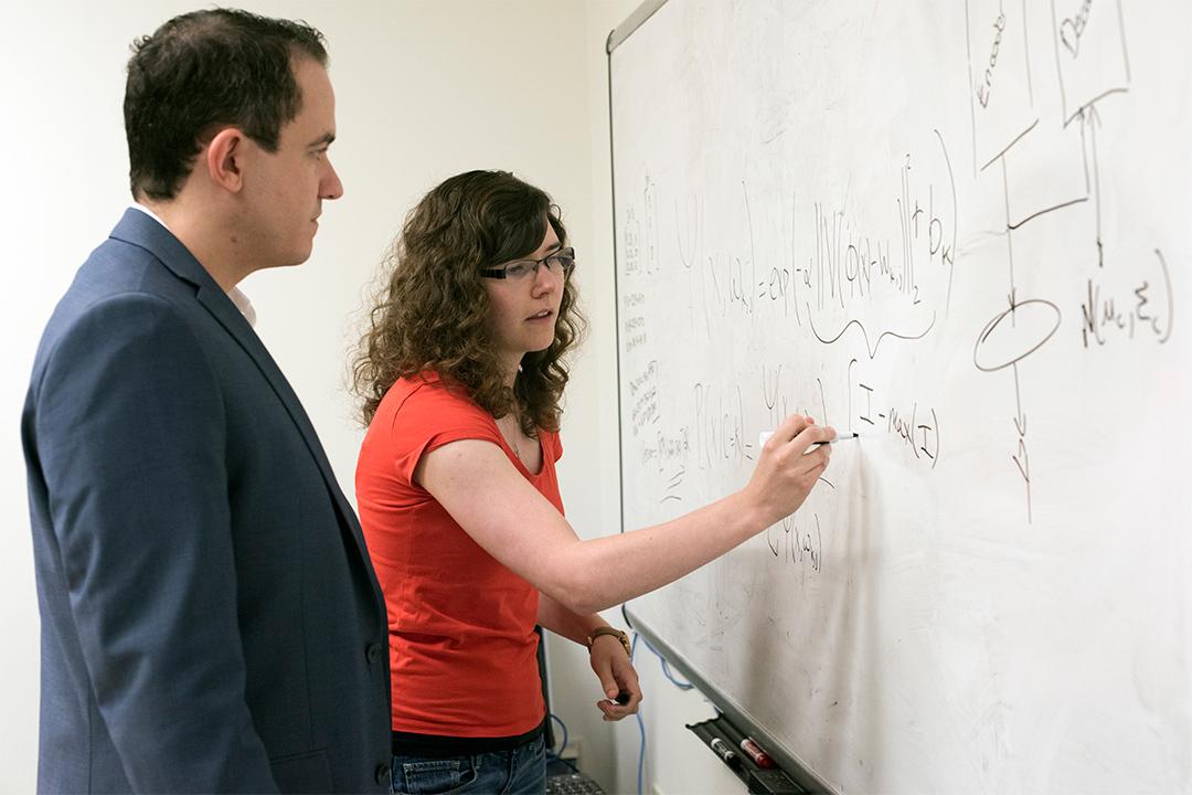 professor watching student write on dry-erase board.