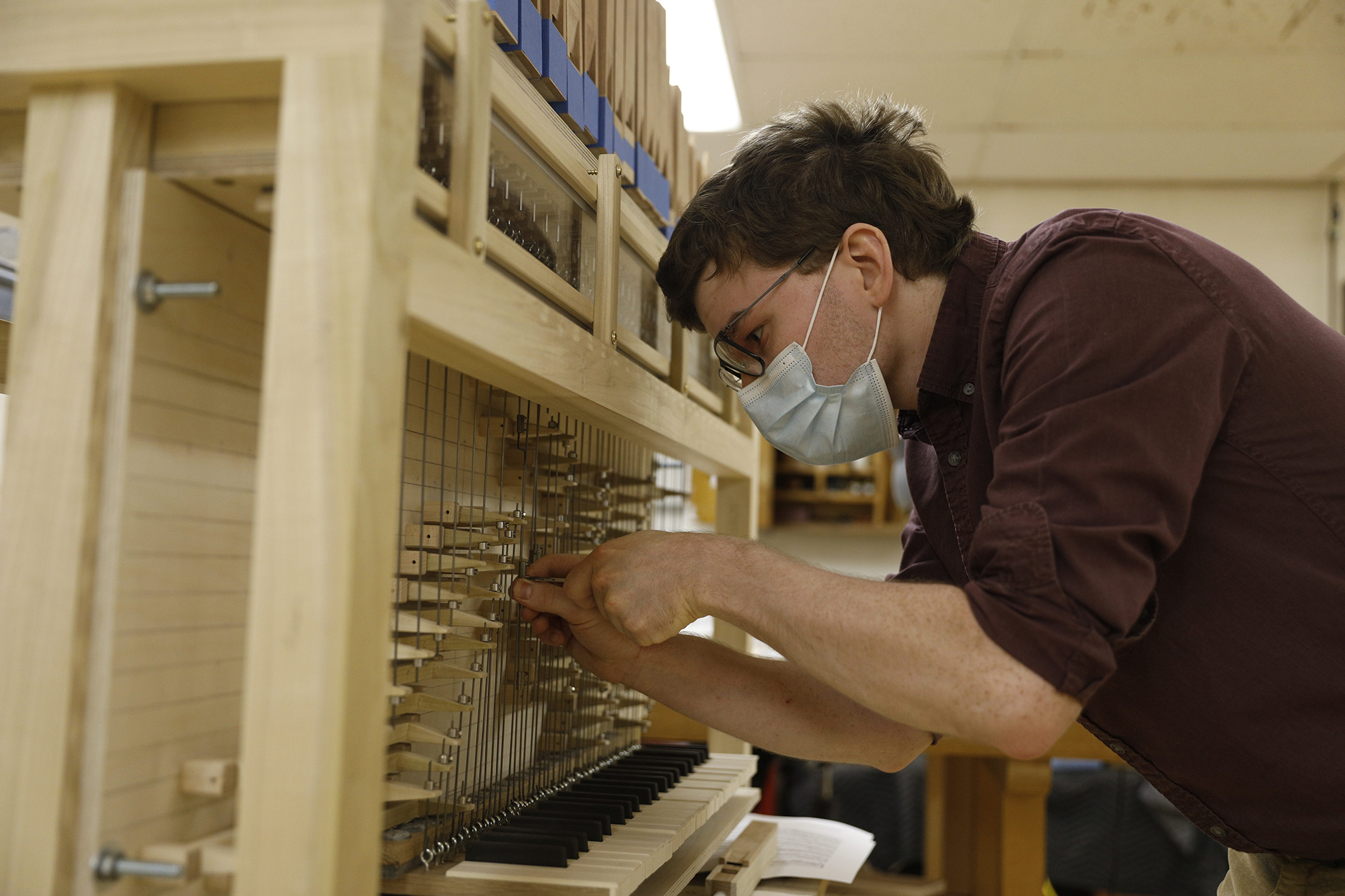 Kelly Cleveland uses a hand tool to adjust the mechanics of his pipe organ.