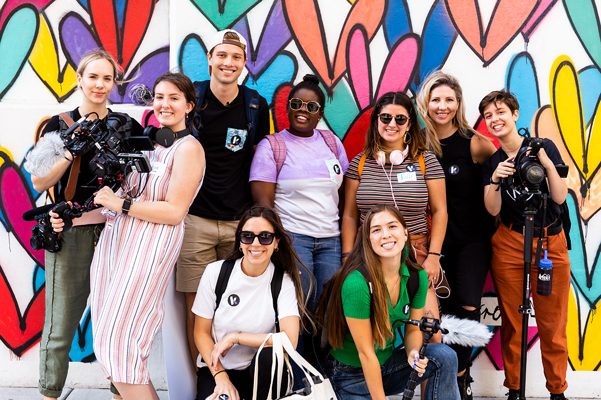 A group of people pose for a photo in front of a colorful wall.