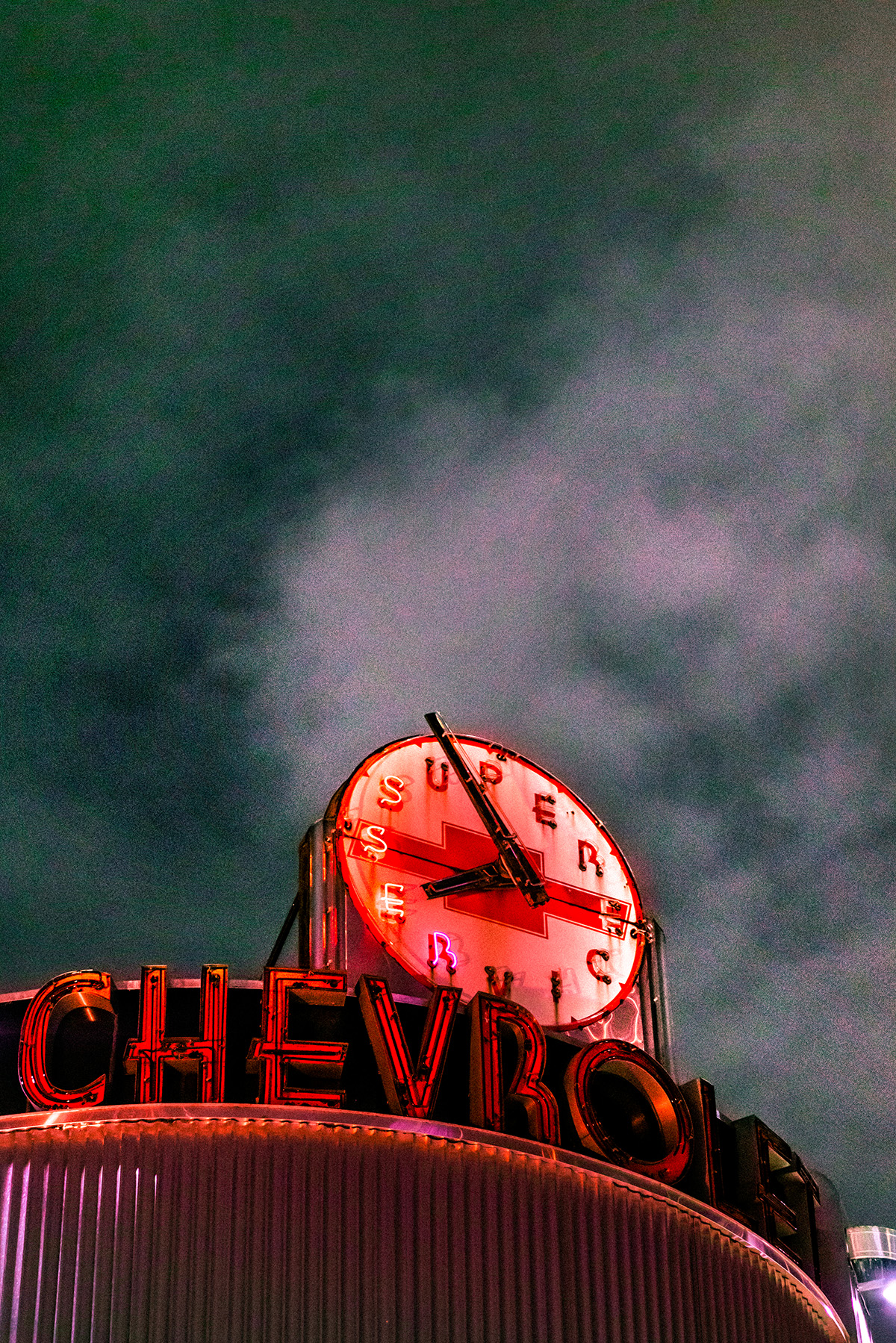 A photo of the top of a building with a clock, beneath a dark, night sky.