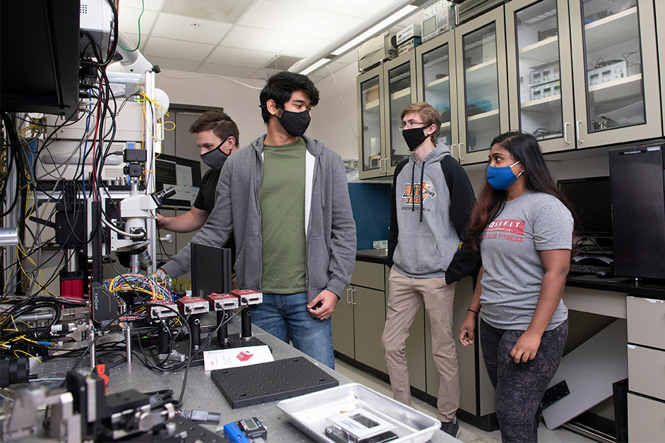 student researchers wearing masks and working in a lab.