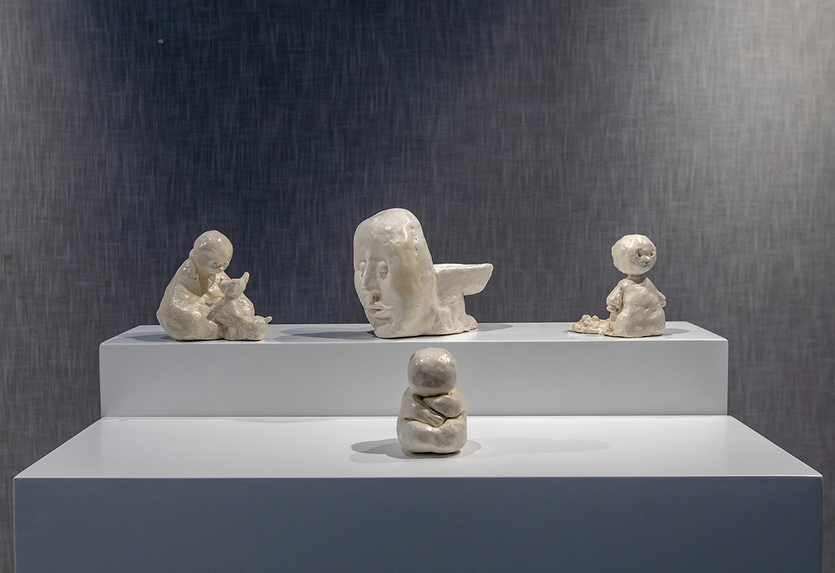 Four ceramic sculptures sit on a surface.