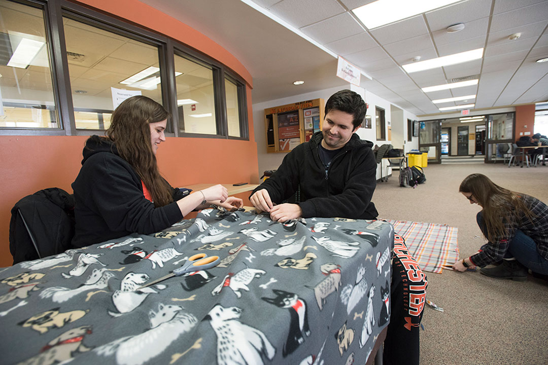 Two students sit at a table and one kneels on the ground. All are making blankets.