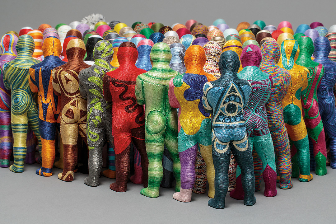 Crowd of figurines made of yarn shown from behind.