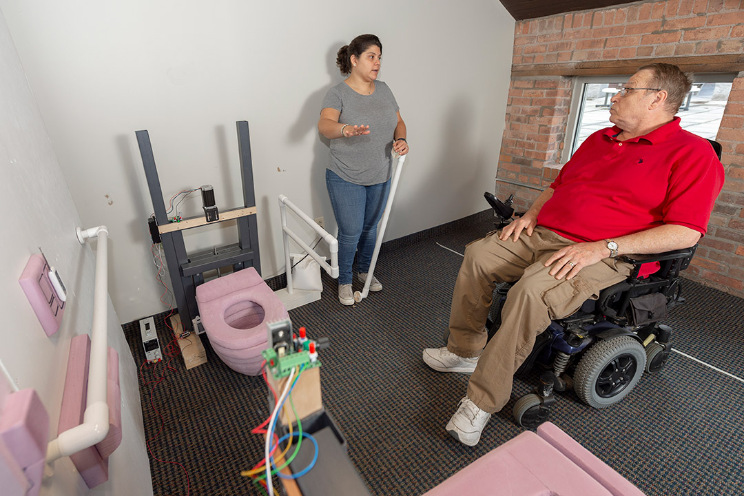 researcher showing prototype of accessbile bathroom to man in wheelchair.
