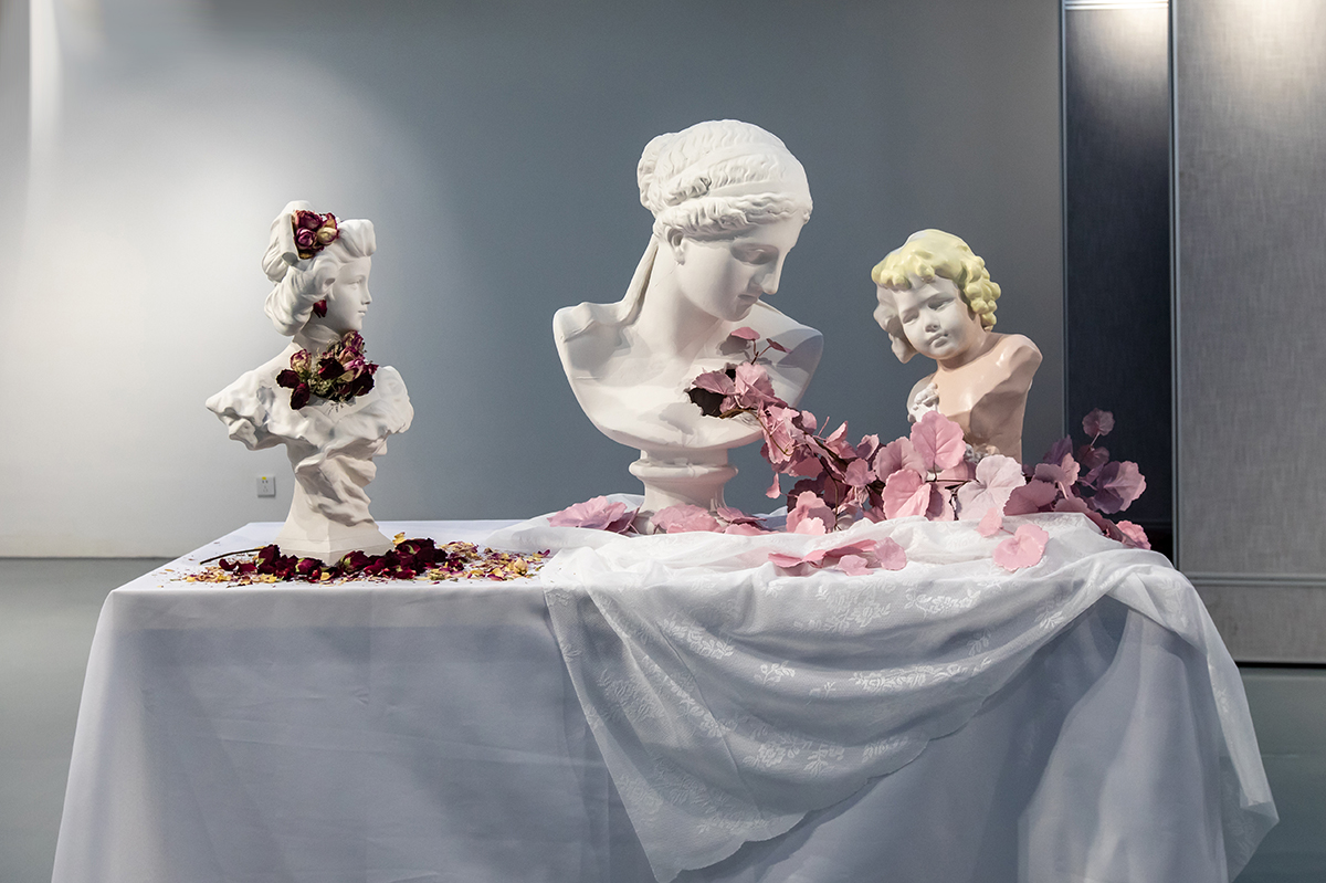 thee sculptures on a table, surrounded by flowers and other symbolism of love.