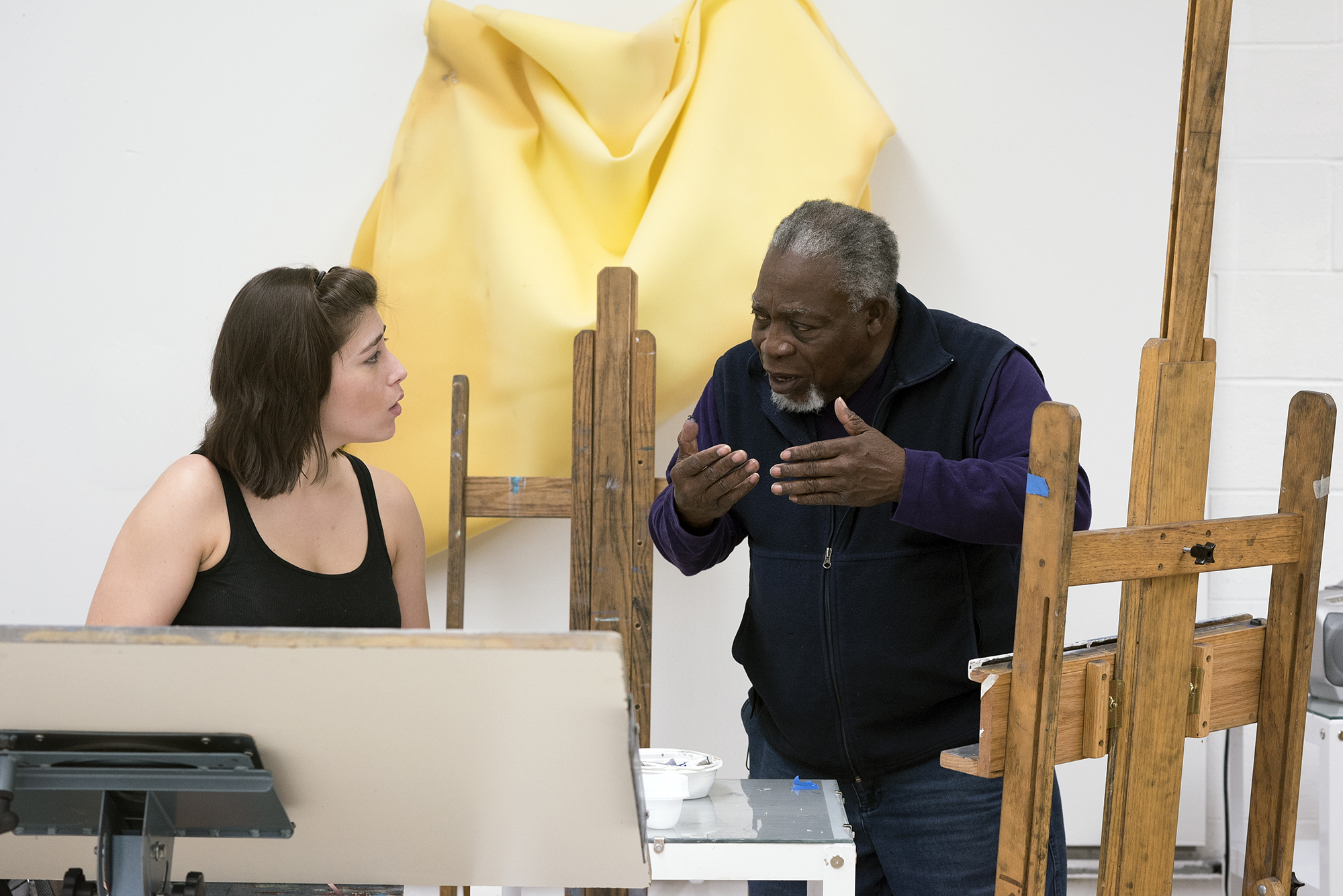Luvon Sheppard talking with a student working on a painting on an easel.