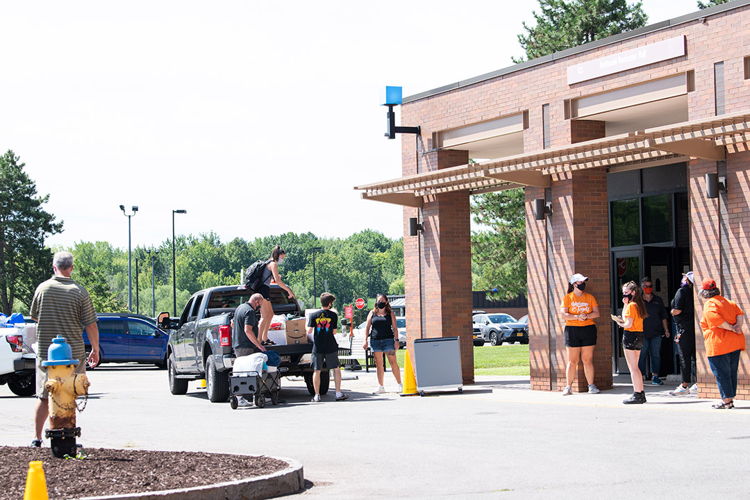 students waiting outside with vehicles to move their belongings into campus housing.