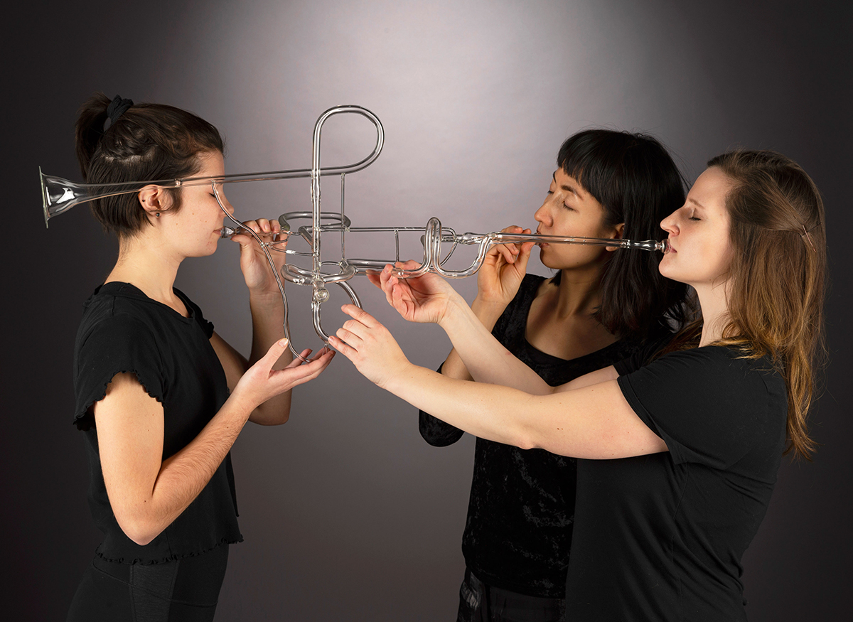Three people play a contemporary glass trumpet.