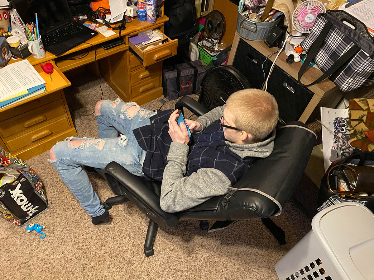 An overhead photo of someone sitting on a chair scrolling through his phone.
