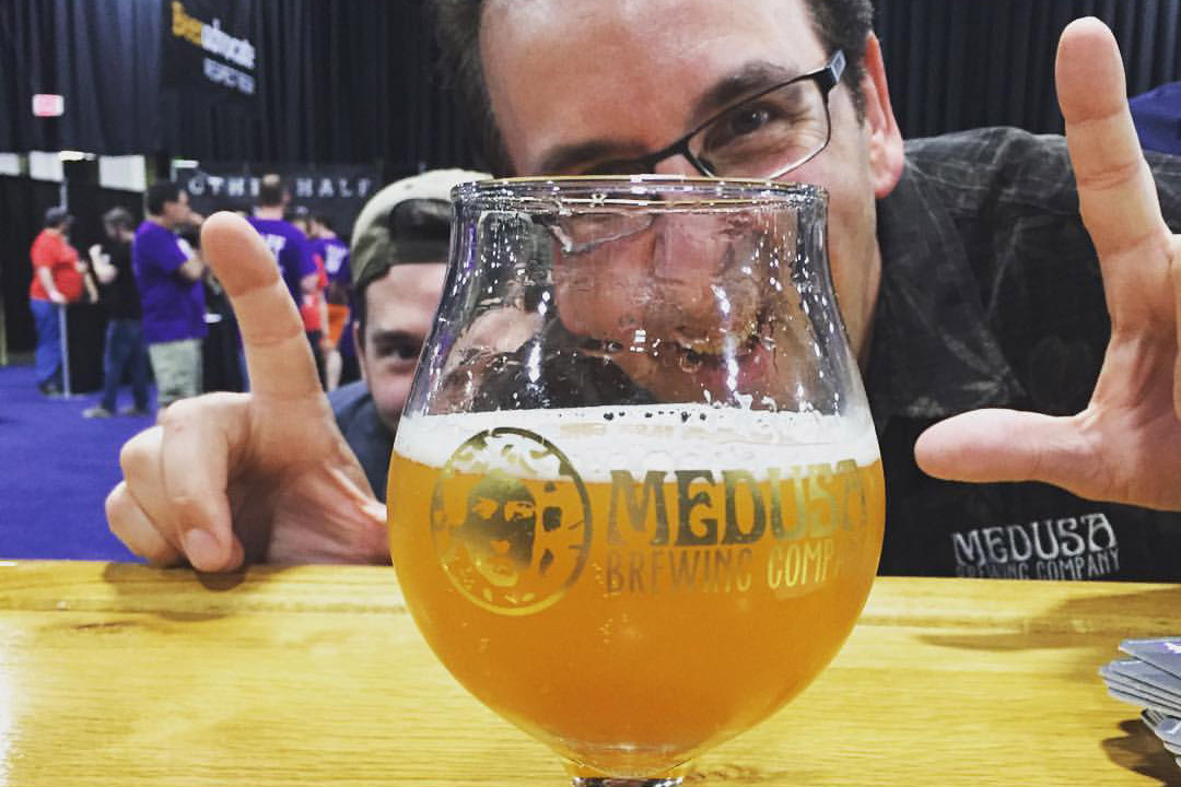 man posing with glass of beer.