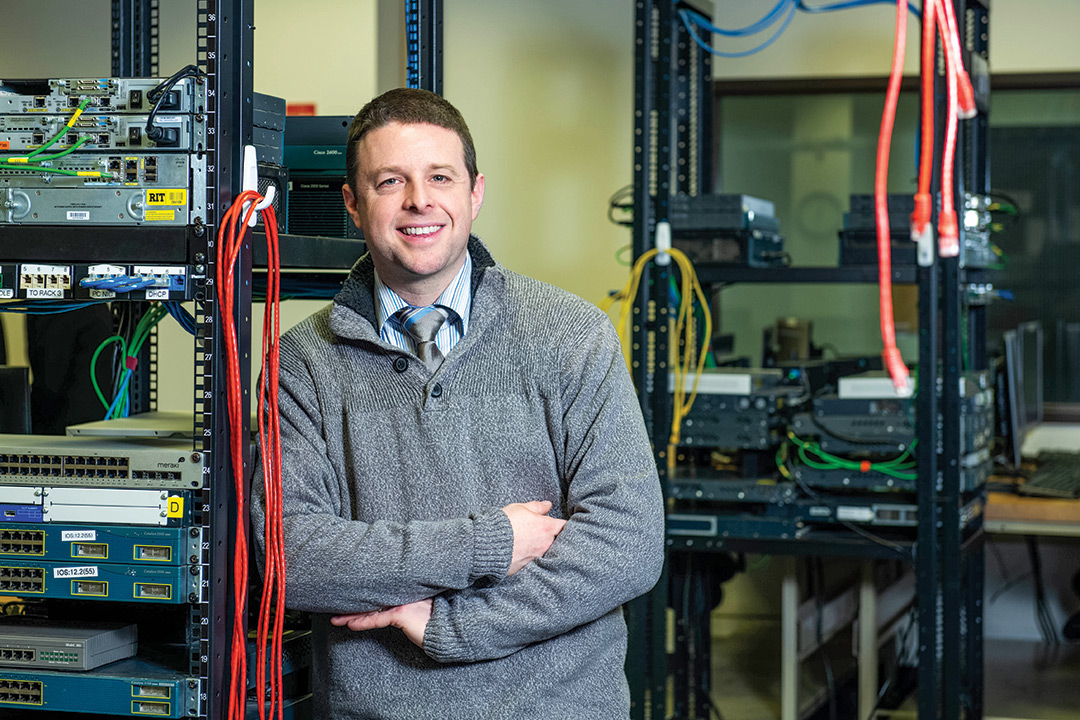 Man stands next to rack of computer servers.