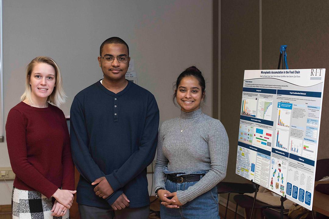three students posing next to poster presentation.