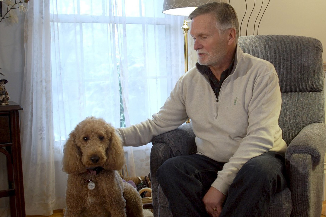 Man sitting in chair with dog sitting on the floor.